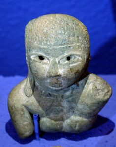 5: Torso de figurilla femenina con tocado y decoración incisa.